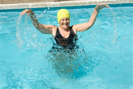 seniors and swim cap - Senior woman splashing in swimming pool, arms raised, laughing Stock Photo - Premium Royalty-Free, Code: 6106-05565842