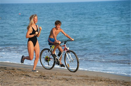 Boy and young woman on beach exercising Stock Photo - Premium Royalty-Free, Code: 6106-05567560