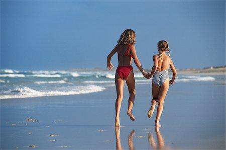 Two girls holding hands, running at beach Stock Photo - Premium Royalty-Free, Code: 6106-05569229