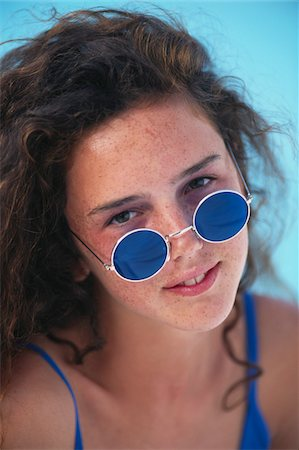 Teenage girl in swimsuit wearing sunglasses, close up Stock Photo - Premium Royalty-Free, Code: 6106-05569308