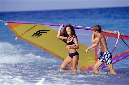 Young woman and teenage boy (16-17) carrying windsurfing sail in sea Stock Photo - Premium Royalty-Free, Code: 6106-05572271