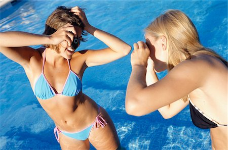 Two teenage girls (16-17) taking pictures in pool Stock Photo - Premium Royalty-Free, Code: 6106-05572411