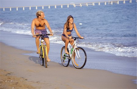 Young couple cycling along beach Stock Photo - Premium Royalty-Free, Code: 6106-05572523
