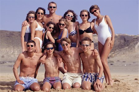 Group of people with two young girls (10-11) and teenage boys (16-17) on beach, portrait Stock Photo - Premium Royalty-Free, Code: 6106-05572913