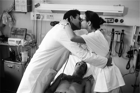 Doctor and nurse kissing over patient in hospital bed, side view, (B&W) Stock Photo - Premium Royalty-Free, Code: 6106-05575813