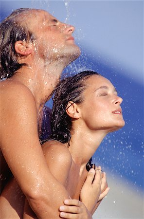 Couple under outdoor shower, head and shoulders Stock Photo - Premium Royalty-Free, Code: 6106-05575989