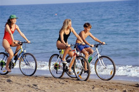 Mother with daughter (16-17) and son (12-13) riding bikes on beach Stock Photo - Premium Royalty-Free, Code: 6106-05576376