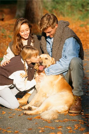 dog kissing man - Parents with daughter (6-7) and dog on walk in forest Stock Photo - Premium Royalty-Free, Code: 6106-05577365