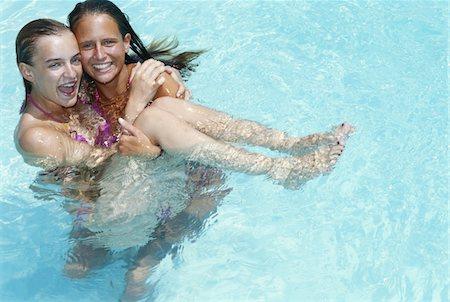 Teenage girls playing in swimming pool Stock Photo - Premium Royalty-Free, Code: 6106-05582661