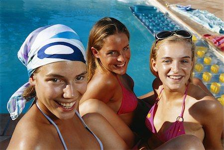 Three teenage girls in bikini sitting by pool Stock Photo - Premium Royalty-Free, Code: 6106-05582677