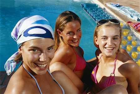 Three teenage girls in bikini sitting by pool Stock Photo - Premium Royalty-Free, Code: 6106-05582677