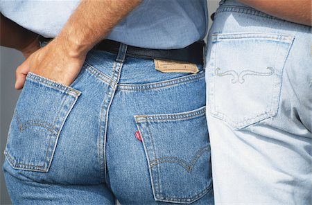 Man with hand in woman's jeans pocket, mid section Stock Photo - Premium Royalty-Free, Code: 6106-05583324