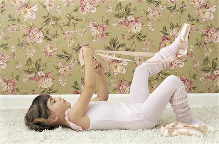 Girl (3-5) lying on back tying ballet shoes, side view Stock Photo - Premium Royalty-Free, Code: 6106-05583525