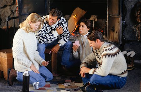sweater and fireplace - Two couples sitting by fireplace, playing card game Stock Photo - Premium Royalty-Free, Code: 6106-05583977