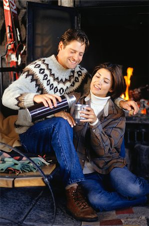 sweater and fireplace - Couple sitting in ski lodge by fireplace, man pouring coffee from insulated flask for woman Stock Photo - Premium Royalty-Free, Code: 6106-05584007