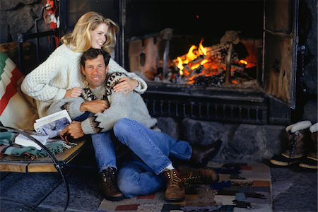 sweater and fireplace - Couple sitting in ski lodge by fireplace, embracing Stock Photo - Premium Royalty-Free, Code: 6106-05584009