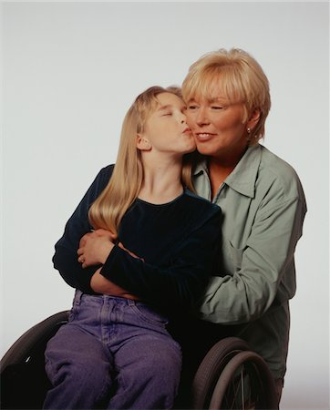 Girl (13-14) in wheel chair kissing mother, posing in studio, portrait Stock Photo - Premium Royalty-Free, Code: 6106-05584268