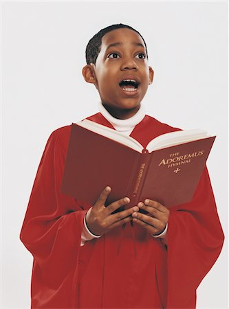 Choirboy in a Red Gown Singing From a Hymn Book Stock Photo - Premium Royalty-Free, Code: 6106-05589042