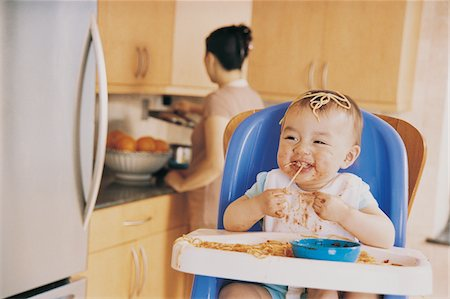 Messy Baby Sitting in a Highchair Eating Spaghetti and its Mother in the Background Stock Photo - Premium Royalty-Free, Code: 6106-05589688