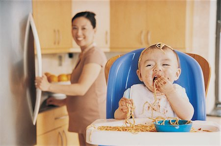 Messy Baby Eating Spaghetti Sitting in a Highchair and its Mother in the Background Stock Photo - Premium Royalty-Free, Code: 6106-05589689