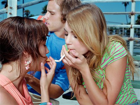 Two Teenage Girls Sit Face to Face Lighting Each Other's Cigarettes Stock Photo - Premium Royalty-Free, Code: 6106-05590115