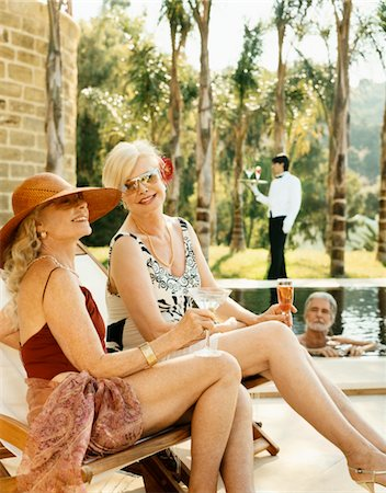 seniors woman in swimsuit - Two Elegant Senior Women in Swimsuits Sit By a Pool, a Senior Man in the Pool and Their Butler in the Background Stock Photo - Premium Royalty-Free, Code: 6106-05590856