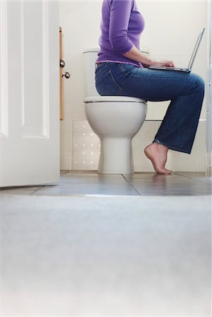 Low Section of a Woman Sitting on a Lavatory Using a Laptop Stock Photo - Premium Royalty-Free, Code: 6106-05590827