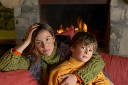 sweater and fireplace - Mother Cuddling Her Son on a Sofa in a Living Room Stock Photo - Premium Royalty-Free, Code: 6106-05592467