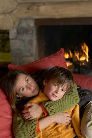 sweater and fireplace - Mother Cuddling Her Son on a Sofa in a Living Room Stock Photo - Premium Royalty-Free, Code: 6106-05592466
