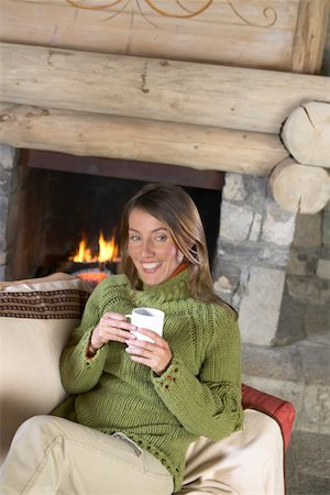 sweater and fireplace - Woman Sitting on a Sofa in a Living Room Wearing a Jumper and Holding a Mug Stock Photo - Premium Royalty-Free, Code: 6106-05592468