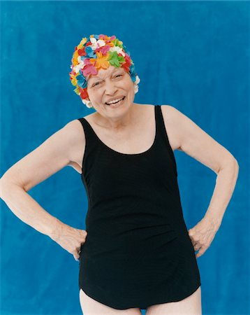 seniors woman in swimsuit - Portrait of a Senior Woman Standing in a Swimming Costume With Her Hands on Her Hips Wearing a Floral Swimming Cap Stock Photo - Premium Royalty-Free, Code: 6106-05592771
