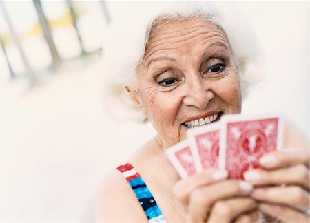 seniors woman in swimsuit - Woman Looking at Her Playing Cards Stock Photo - Premium Royalty-Free, Code: 6106-05594277