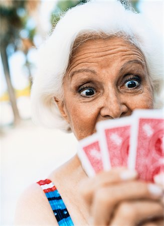 seniors woman in swimsuit - Surprised Looking Woman Looking Down at Her Cards Stock Photo - Premium Royalty-Free, Code: 6106-05594276