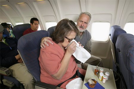 Senior Woman Vomiting Into a Sick Bag During a Flight on a Plane Stock Photo - Premium Royalty-Free, Code: 6106-05594216