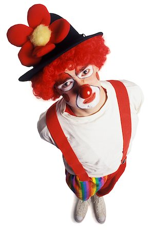 an adult male clown in a funny outfit as he glance up at the camera Stock Photo - Premium Royalty-Free, Code: 6106-05595384