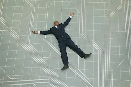 conceptual shot of an african american business man as he lays flat on the ground holding his phone Stock Photo - Premium Royalty-Free, Code: 6106-05595810