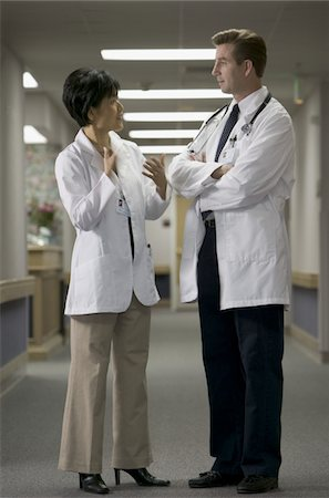 two adult doctors stand together and talk back and forth in the hallway of a hospital Stock Photo - Premium Royalty-Free, Code: 6106-05595904