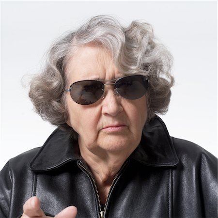 portrait of an elderly caucasian woman in a leather jacket and sunglasses as she points at the camera and scowls Stock Photo - Premium Royalty-Free, Code: 6106-05596078