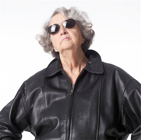 portrait of an elderly caucasian woman in a leather jacket and sunglasses as she throws her head back confidently Stock Photo - Premium Royalty-Free, Code: 6106-05596079