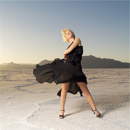 desert people dress photos - a young blonde woman dressed in a black dress tosses her skirt in a desert setting Stock Photo - Premium Royalty-Free, Code: 6106-05596455