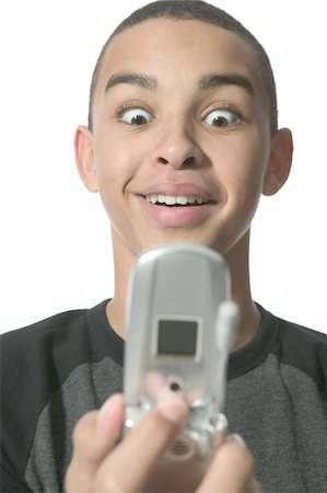 an african american teenage male acts surprised as he gets info of his cell phone Stock Photo - Premium Royalty-Free, Code: 6106-05596562