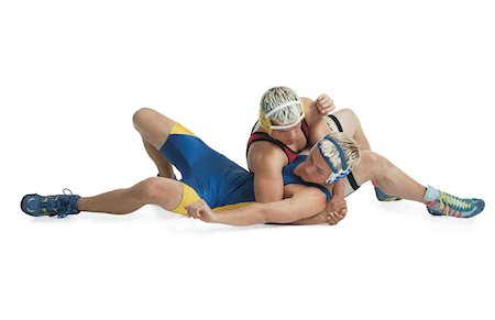 two teenage caucasian male wrestlers from opposing teams stuggle on the mat and the one in red tries to pin the one in blue Stock Photo - Premium Royalty-Free, Code: 6106-05598456