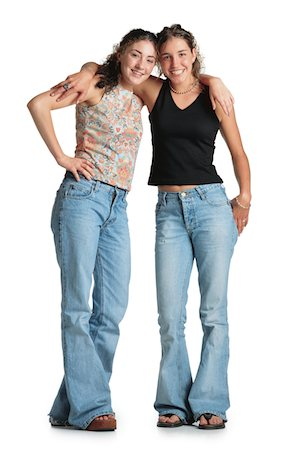 female white background full body - two teenage girls with curly brown hair stand with their arms around each others shoulders wearing tank tops and blue jeans they smile at the camera Stock Photo - Premium Royalty-Free, Code: 6106-05598884