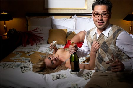 Man and prostitute in bedroom, dollar banknotes scattered around Stock Photo - Premium Royalty-Free, Code: 6106-05501678