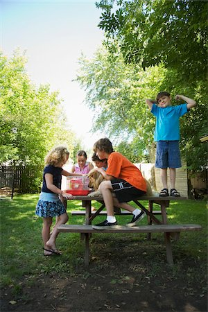 Group of children (7-13) with dog sitting on picnic table, looking at hamster in cage Stock Photo - Premium Royalty-Free, Code: 6106-05504848