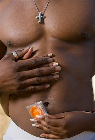 Woman wrapping hands (close-up of hands) around man (mid section) while holding wrapped condom Stock Photo - Premium Royalty-Free, Code: 6106-05506276
