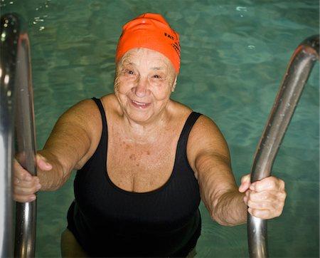 seniors and swim cap - Elderly woman climbing out of swimming pool Stock Photo - Premium Royalty-Free, Code: 6106-05508780