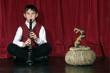 Boy (8-9) playing clarinet on stage charming snake Stock Photo - Premium Royalty-Free, Code: 6106-05509613