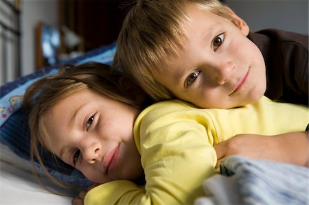 Portrait of brother and sister (5-8) lying down in bed Stock Photo - Premium Royalty-Free, Code: 6106-05509630