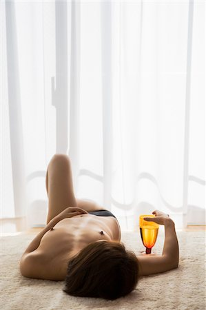 Shirtless woman lying on floor in room with glass of water Stock Photo - Premium Royalty-Free, Code: 6106-05509999